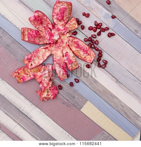 Composition With Pomegranate Peel And Pomegranate Seeds On Wooden Background.