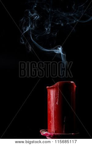 smoke goes up from the extinct red candle
