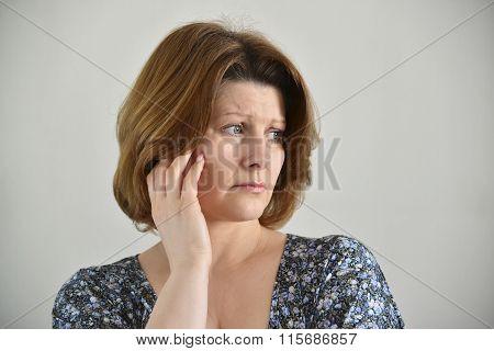 Portrait of adult sad female on light background