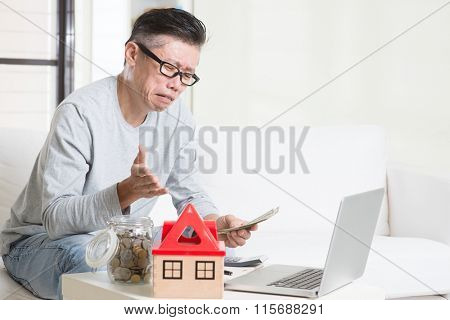Cash flow problem concept. Portrait of 50s mature Asian man counting money with worried expression, sitting on sofa at home.