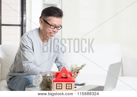 Portrait of 50s mature Asian man counting on money. Saving, retirement, retirees financial planning concept. Family living lifestyle at home.
