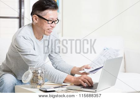 Portrait of 50s mature Asian man looking at laptop and paying bills online in the living room. Saving, retirement, retirees financial planning concept.