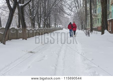 Loving couple walks alongside on an empty street despite of snow and cold