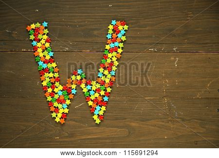 Letter W from alphabet made with star shape candy on a wooden background