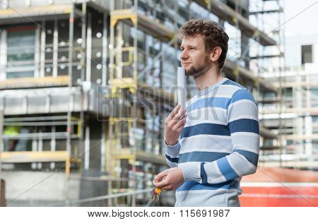 Man With Keys On Front Of New House Building