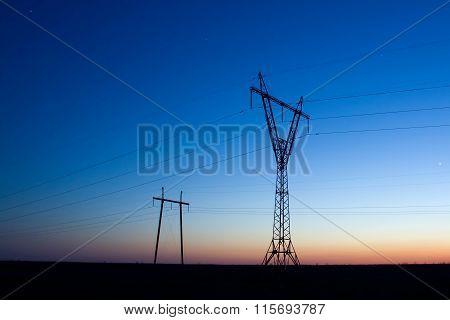 Silhouette Of Electricity Transmission Pylon On Blue Sky