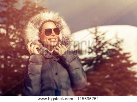 Portrait of beautiful woman having fun in the winter park, wearing sunglasses and coat with fur hood in frosty sunny day, stylish wintertime look