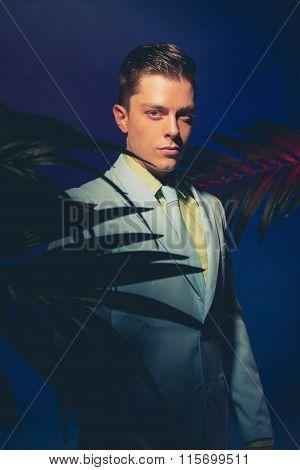 Handsome Man In Formal Wear Between Palm Leaves