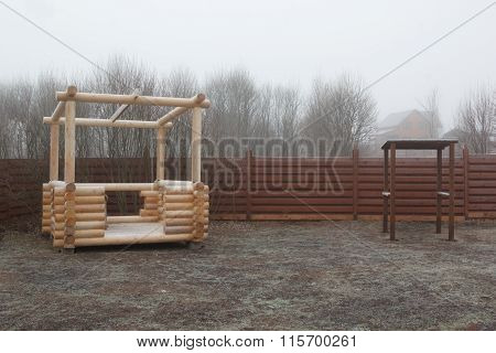 Log Gazebo In Frozen Garden In Mist