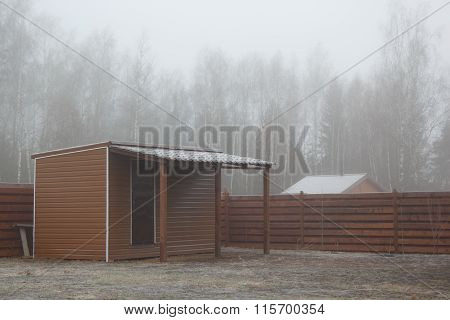 Barn With Shed On Frozen Lawn In Mist