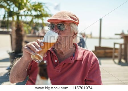 Senior Man Enjoying An Ice Cold Beer