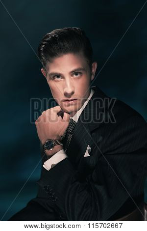 Retro Fashion Man In Suit And Tie Holding His Chin. Hair Combed Back. Dark Blue Background. Studio S
