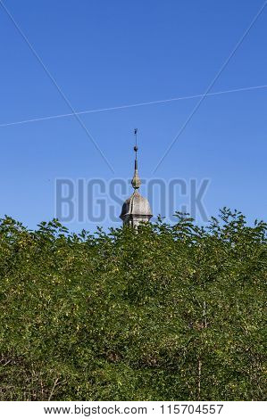 Top Of A Steeple Hidden Behind Trees With Blue Sky