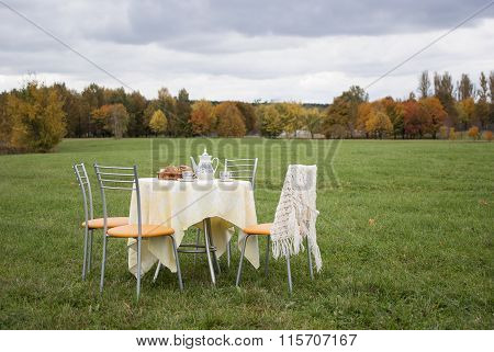 Setout Tea Table  Surrounded By Chairs On The Field Outdoors