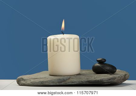 Lit Candle On A Rock.