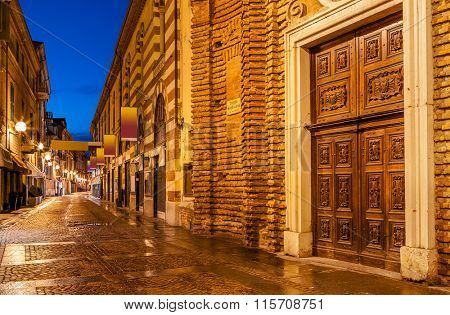 Wet cobbled pedestrian street in evening in Alba, Piedmont, Northern Italy.