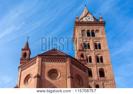 Facade of San Lorenzo Cathedral under blue sky in Alba, Italy.