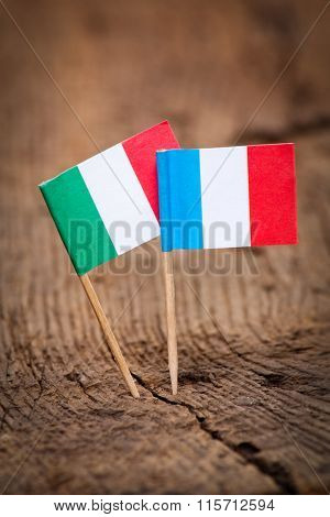Flags of Italy and France on wooden background