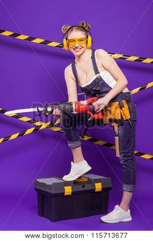 Sexy Blonde Woman On A Purple Background With An Electric Jigsaw With Tool Belt And Stands On A Tool