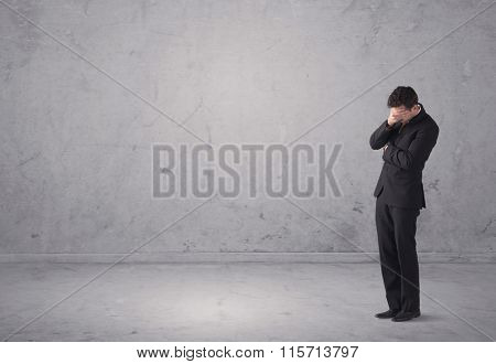 A surprised young sales person in elegant suit standing in empty urban environment with grey concrete wall background concept
