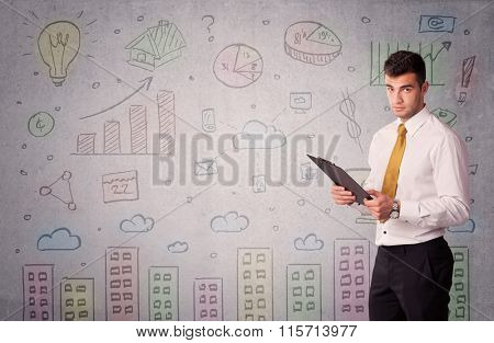 A young adult businessman standing in front of a wall with colorful drawings of buildings, charts, graphs, signs concept