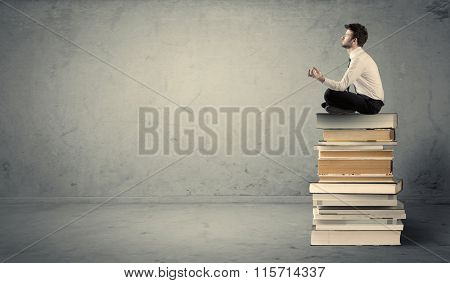 A serious student in elegant suit sitting on a pile of books in front of grey background