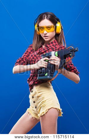 Waist Picture Sexy Girl-builder In Hearing Protection And Protective Glasses Yellow On A Blue Backgr