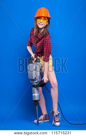 Girl On A Blue Background In The Construction Helmet And Protective Goggles Holding A Jackhammer
