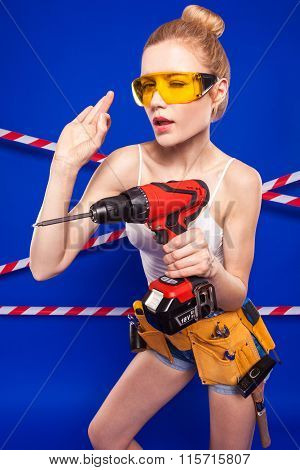 Blonde On A Blue Background With A Tape Construction Fencing With Screwdriver In Hands
