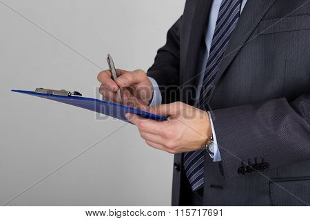 Business Man Holding Clipboard And Signing Documents