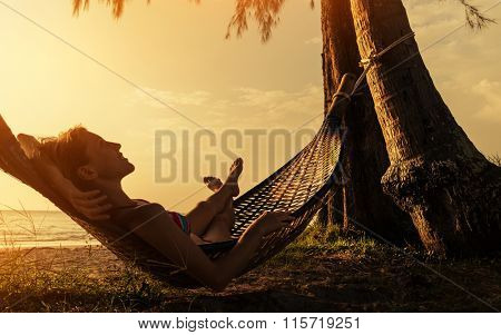 Lady relaxing in the hammock on the beach
