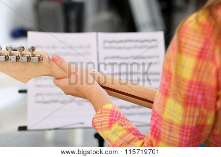 Female Hand Holding Wooden Neck Of Electric Guitar