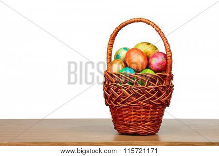 Painted easter eggs in a wicker basket on a table isolated on white background