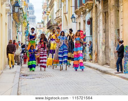 HAVANA,CUBA- JANUARY 24,2015 : Colorful band of musicians and dancers on stilts on a narrow Old Havana street