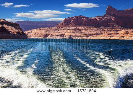 Foamy trace of a motor boat crosses the emerald waters. Red sandstone hills surround the lake. Lake Powell on the Colorado River
