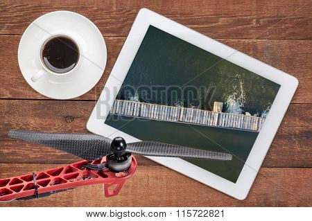 aerial landscape photography concept - reviewing aerial pictures of  a river diversion dam on a digital tablet with a drone propeller in foreground, screen picture copyright by the photographer