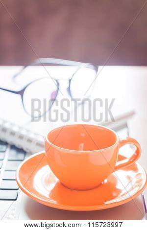 Laptop With Coffee Cup And Notepad On Desk