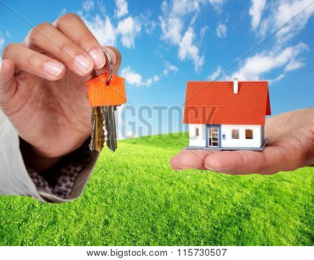 Hand with a little house and keys.