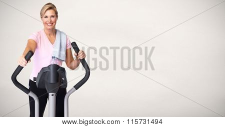 Mature woman doing exercise on elliptical trainer.