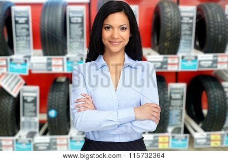 Auto dealer woman near a car tire.