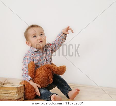 Studio Shot Of Little Boy Point His Finger With His Toy And Books