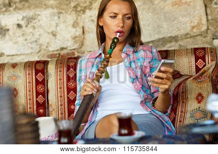 Woman Smoking A Hookah And Using Smartphone In A Cafe In Istanbul, Turkey
