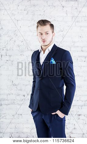 Handsome young businessman adjusting his sleeves while standing against grey background