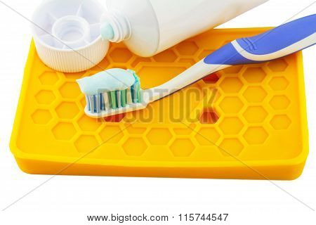 Toothbrush Beside Toothpaste On Yellow Holder Isolated On White Background.