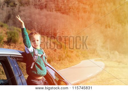 happy little boy travel by car in autumn nature