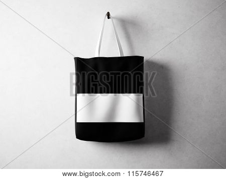 Black cotton textile bag with white line in center holding, neutral background. Horizontal, 3d rende