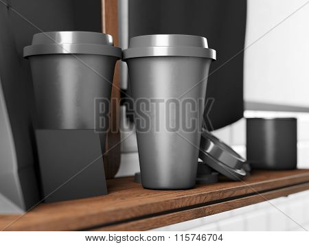 Set of two black take away cups, blank business cards on bookshelf. 3d render