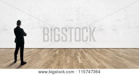 Businessman stands opposite bricks wall in gallery interior with wooden floor.