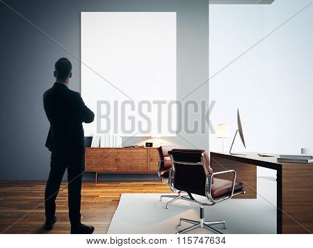 Businessman stands in modern office with empty white canvas