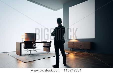 Businessman stands in modern office with empty canvas. Color